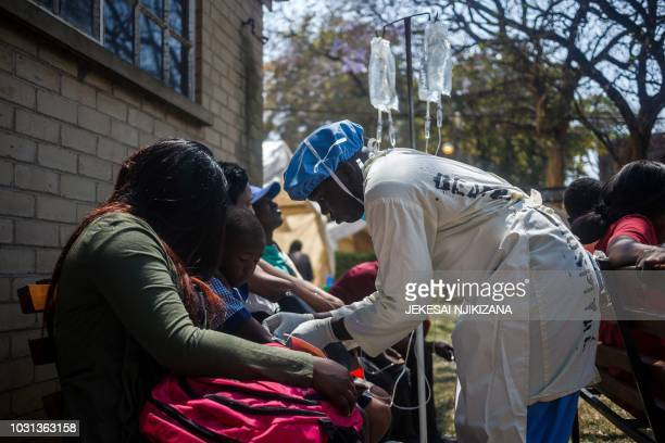 A nurse takes care of cholera patients during a visit of Zimbabwe Minister of Health at the cholera treatment centre of the Beatrice Infectious...