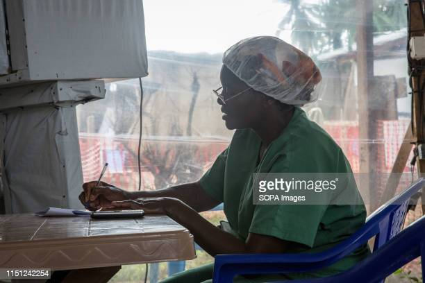 A nurse takes notes beside an isolation unit at the Ebola treatment centre in Beni eastern Democratic Republic of the Congo The DRC is currently...
