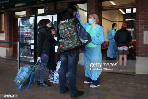 Nurse takes the temperature of arriving rail passengers from Melbourne at Central Station on July 03, 2020 in Sydney, Australia. The NSW state...