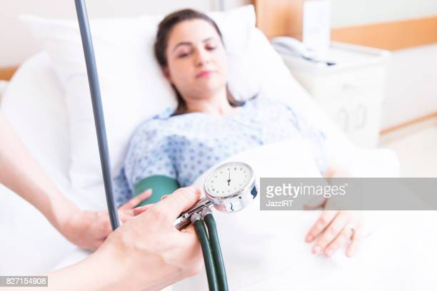 Nurse taking blood pressure of patient