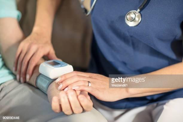 Nurse taking blood pressure of senior patient at home