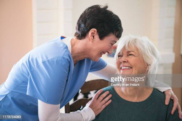 nurse taking care of elderly lady - cuidado fotografías e imágenes de stock