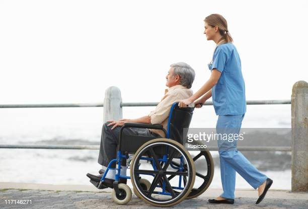 Nurse taking patient for a stroll on pier