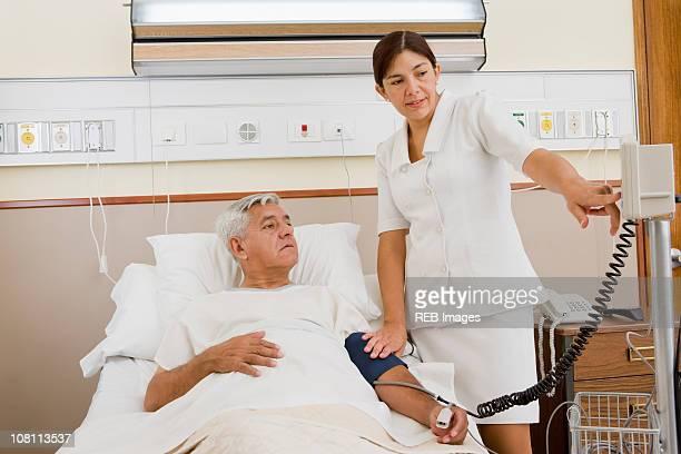 Nurse taking patient's blood pressure in hospital room