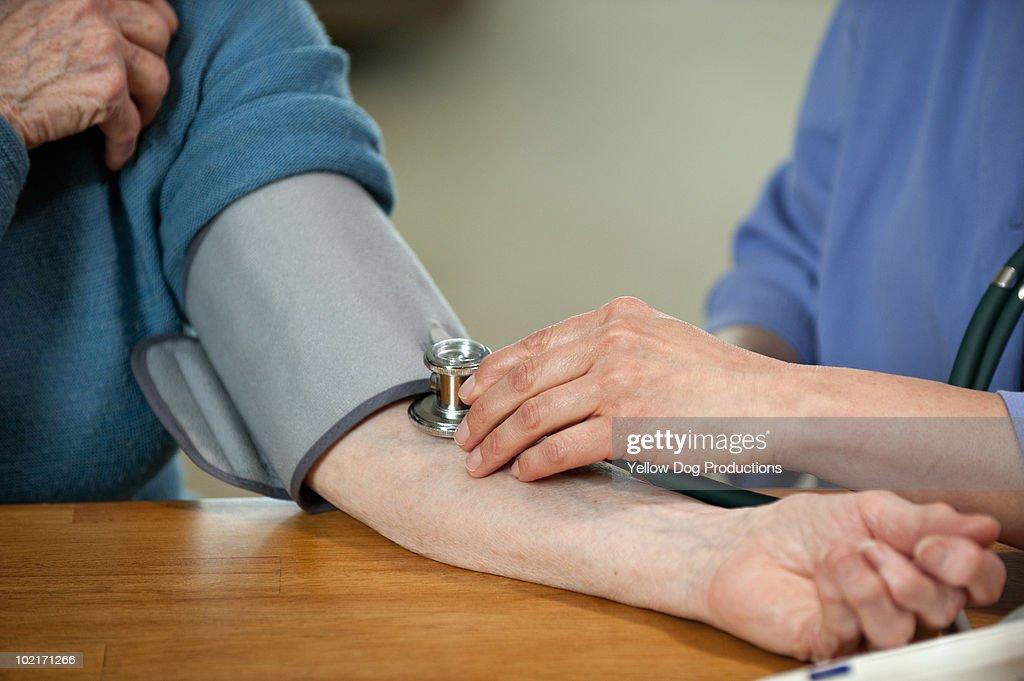 Nurse taking patient's blood pressure : Stock Photo