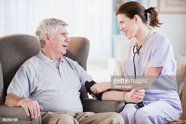 Nurse taking senior mans blood pressure