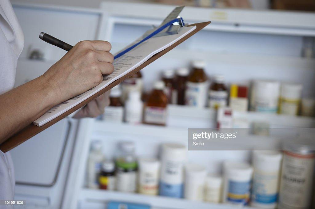 Nurse taking stock of pharmaceutical drugs : Stock Photo