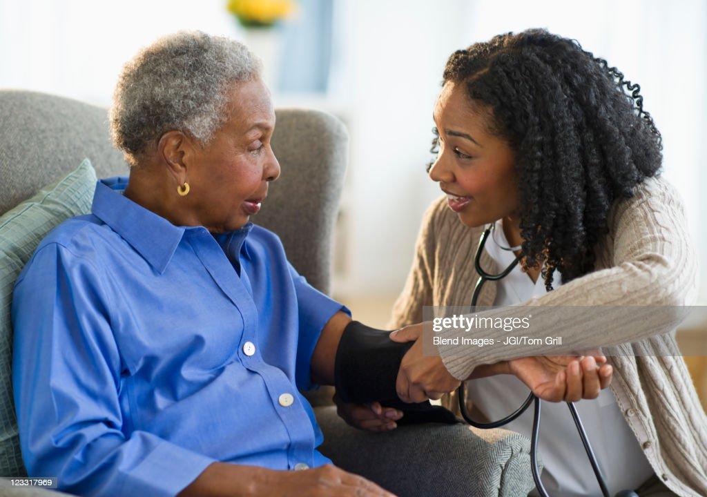 Nurse taking woman's blood pressure : Stock Photo