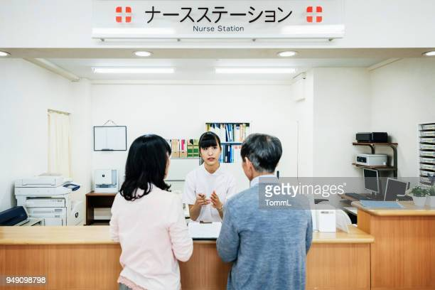 nurse talking to couple in japanese hospital - medical receptionist uniforms stock photos and pictures