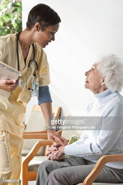 nurse talking to elderly woman - gerontology stock pictures, royalty-free photos & images
