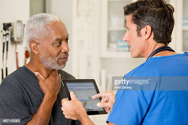 nurse talking to patient in doctor's office - throat photos stock photos and pictures