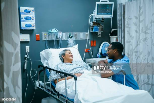 nurse talking to patient in hospital bed - emergency room stock pictures, royalty-free photos & images