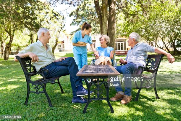 enfermera hablando con la mujer mayor en el hogar de ancianos - izusek fotografías e imágenes de stock