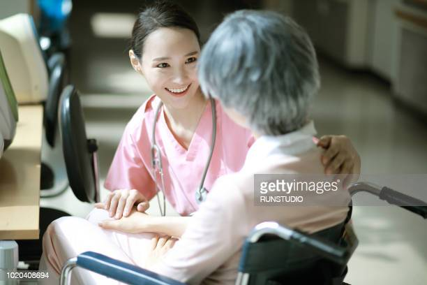 nurse talking to senior woman in wheelchair - 医療とヘルスケア ストックフォトと画像