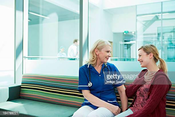 Nurse talking to woman in hospital waiting room