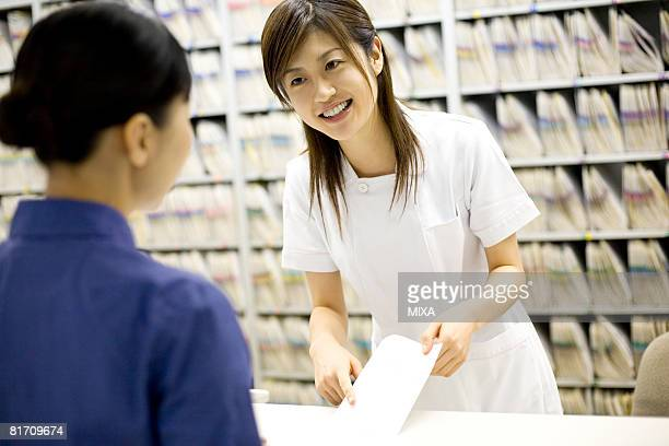 Nurse talking with patient at reception