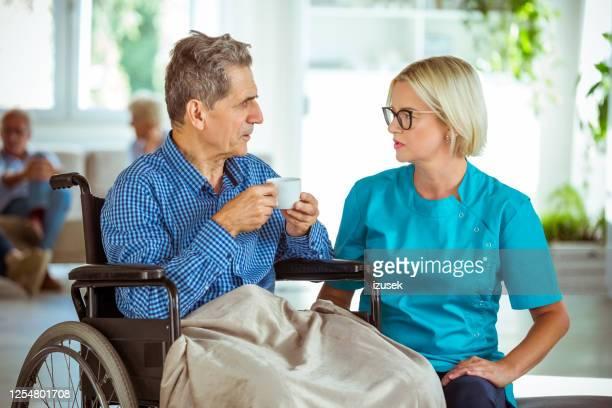 krankenschwester im gespräch mit senior in seniorenhaus - izusek stock-fotos und bilder
