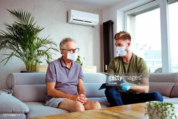 enfermera hablando con una mujer de edad mayor durante la visita a casa - izusek fotografías e imágenes de stock