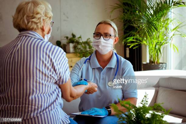 nurse talking with senior woman during home visit - healthcare worker stock pictures, royalty-free photos & images