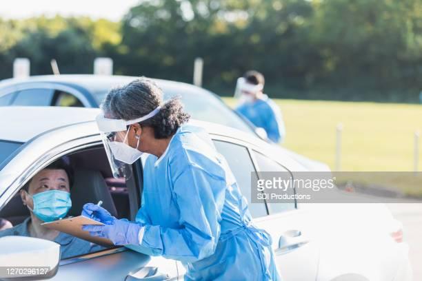 看護師は、covidのテストサイトで並べて患者と話します - ドライブスルー検査 ストックフォトと画像