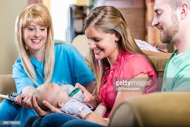 Nurse teaching parents how to give newborn baby breathing treatment