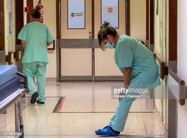 Nurse technician wearing protective mask shows her tiredness at the end of her shift in the intermediate ward for COVID-19 Coronavirus patients in...