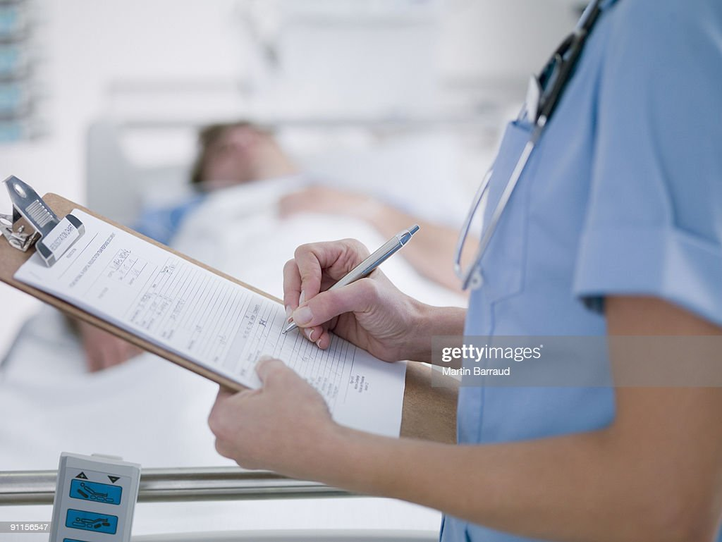 Nurse tending patient in intensive care : Stock Photo