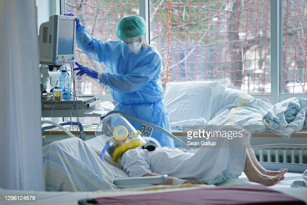Nurse tends to an elderly Covid patient who is wearing a helmet-based ventilation system in the Covid intensive care unit at Leipzig university...
