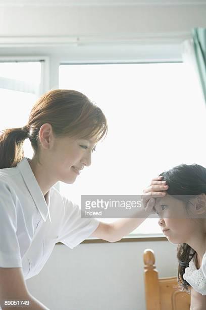 Nurse touching girl's forehead