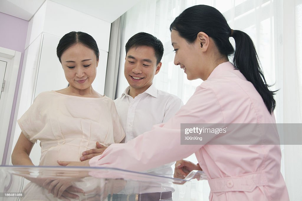 Nurse touching pregnant woman's belly in the hospital with husband beside her : Stock Photo