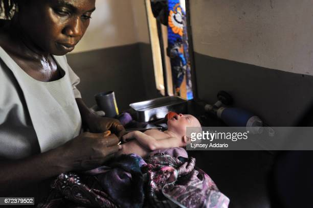 A nurse tries to resuscitate the secondborn twin of Mamma Sessay after she was delivered roughly 24 hours after the first child at the Magburaka...