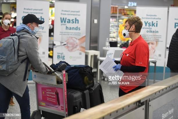 Nurse Tuulikki Seppälä of EMA Finland gives coronavirus information to passengers coming from Amsterdam at the Helsinki Airport in Vantaa Finland on...