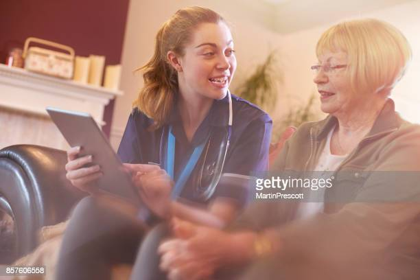 nurse updating patients medical records - nhs stock photos and pictures