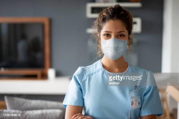 enfermeira usando uma máscara facial enquanto fazia uma chamada em casa durante a pandemia covid-19 - profissional de enfermagem - fotografias e filmes do acervo