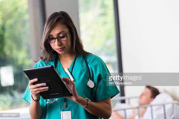 nurse using digital patient chart while taking care of patient - cute nurses stock pictures, royalty-free photos & images