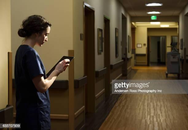 nurse using digital tablet in hospital - überstunden machen stock-fotos und bilder