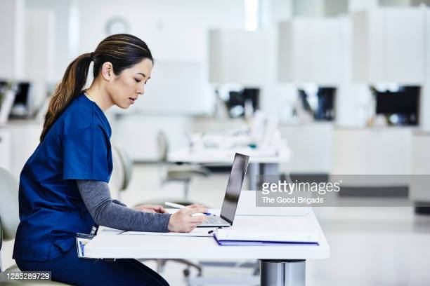nurse using laptop in medical lab - healthcare stock pictures, royalty-free photos & images
