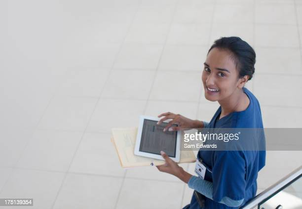 Nurse using tablet computer in hospital hallway