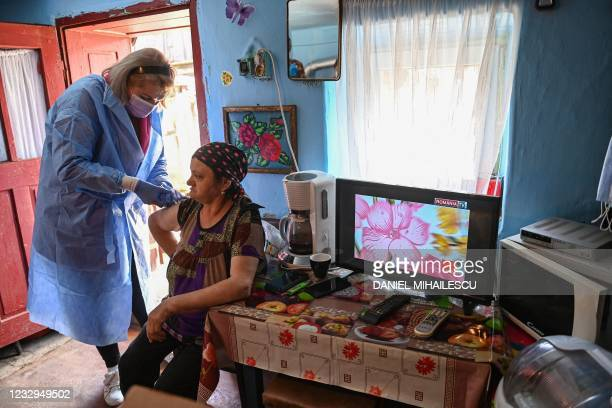 Nurse vaccinates a woman against COVID-19 in the remote village of Poienita Voinii, Romania, on May 13, 2021. - More than 3.8 million people among...