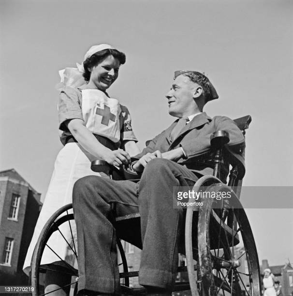 Nurse Violet Morse tends to British Army soldier Gunner Wason seated in a wheelchair in the grounds of Shenley Hospital, a military hospital at...