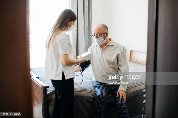 nurse visiting senior male at home doing blood pressure measurement - cardiologist stock pictures, royalty-free photos & images