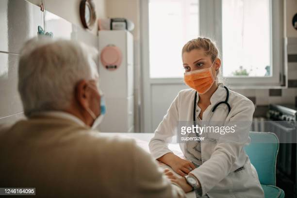 nurse visiting senior man - patience stock pictures, royalty-free photos & images