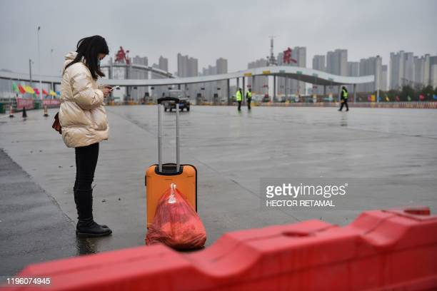 A nurse waits for transportation as she reenters the city to return to Wuhan Yaxin General Hospital on one of the roads blocked by the police to...