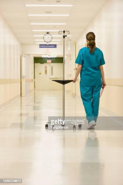 verpleegkundige wandelen down ziekenhuis hal met iv infuus - operatiekleding stockfoto's en -beelden