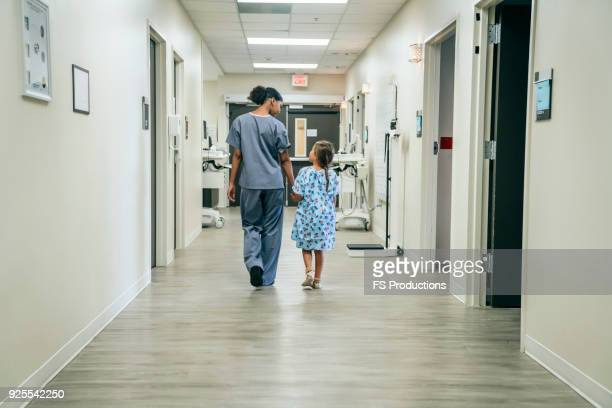 nurse walking with girl in hospital corridor - medical building stock pictures, royalty-free photos & images