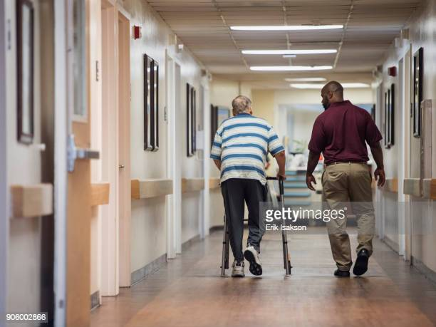 nurse walking with patient using walker - african american man helping elderly stock pictures, royalty-free photos & images