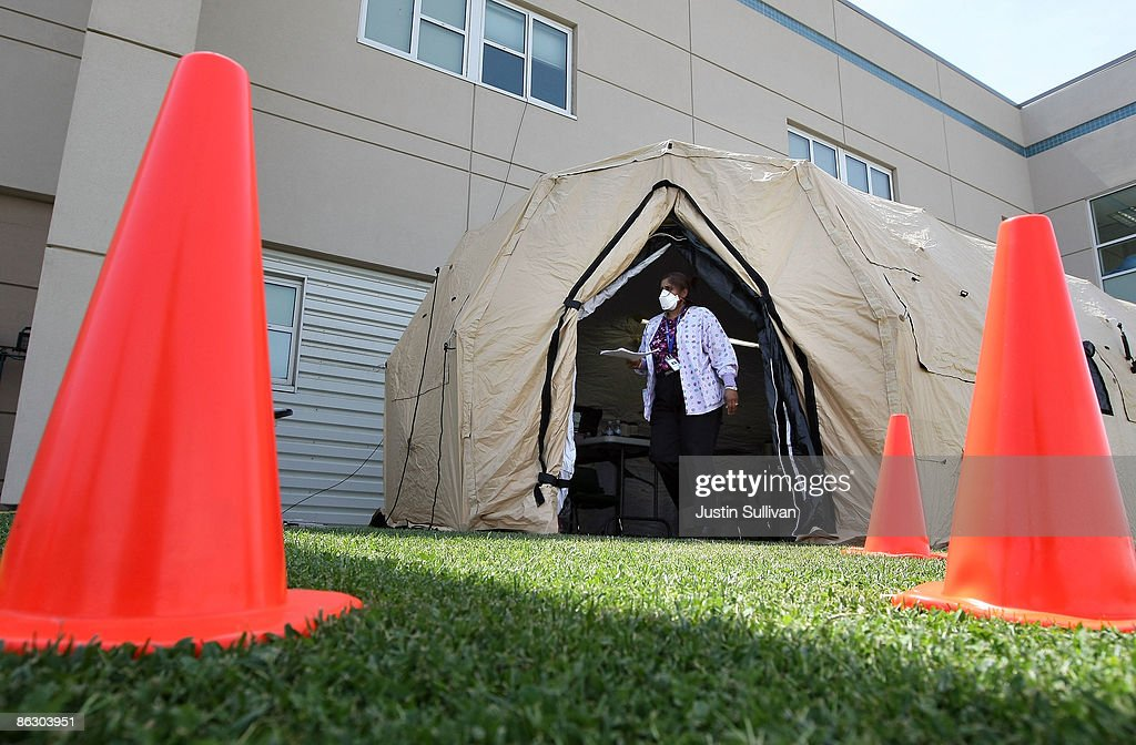A Nurse Walks Out Of A Triage Tent That Was Set Up Outside