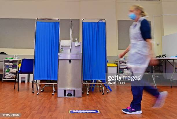 Nurse walks past booths at a Covid-19 vaccination centre in Derby, central England on September 20, 2021. - Frontline health and social care workers,...