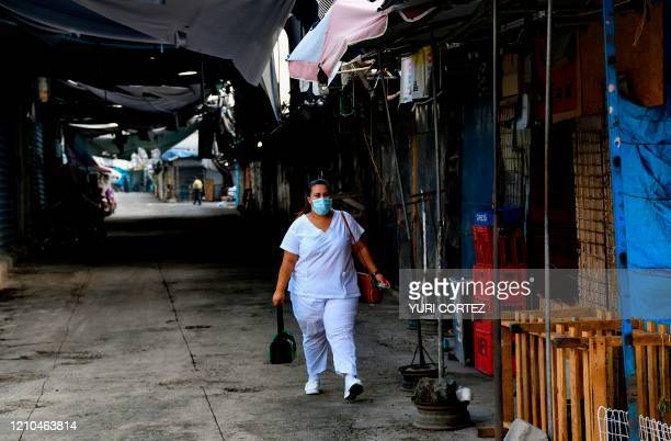 Nurse walks to work along a desolate street in the historic centre of San Salvador, inside a sanitary perimeter imposed by the capital's municipality...