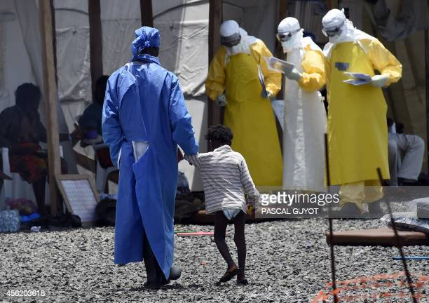 A nurse walks with a little girl suffering from Ebola at the international medical NGO Medecins Sans Frontieres in Monrovia on September 27 2014...